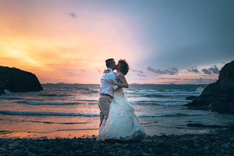 wedding photographer south wales couple kissing on beach at sunset